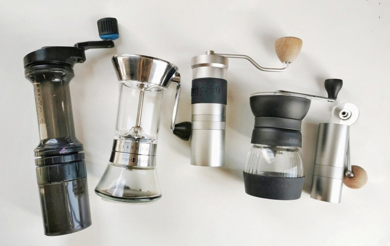 five manual coffee grinders next to each other